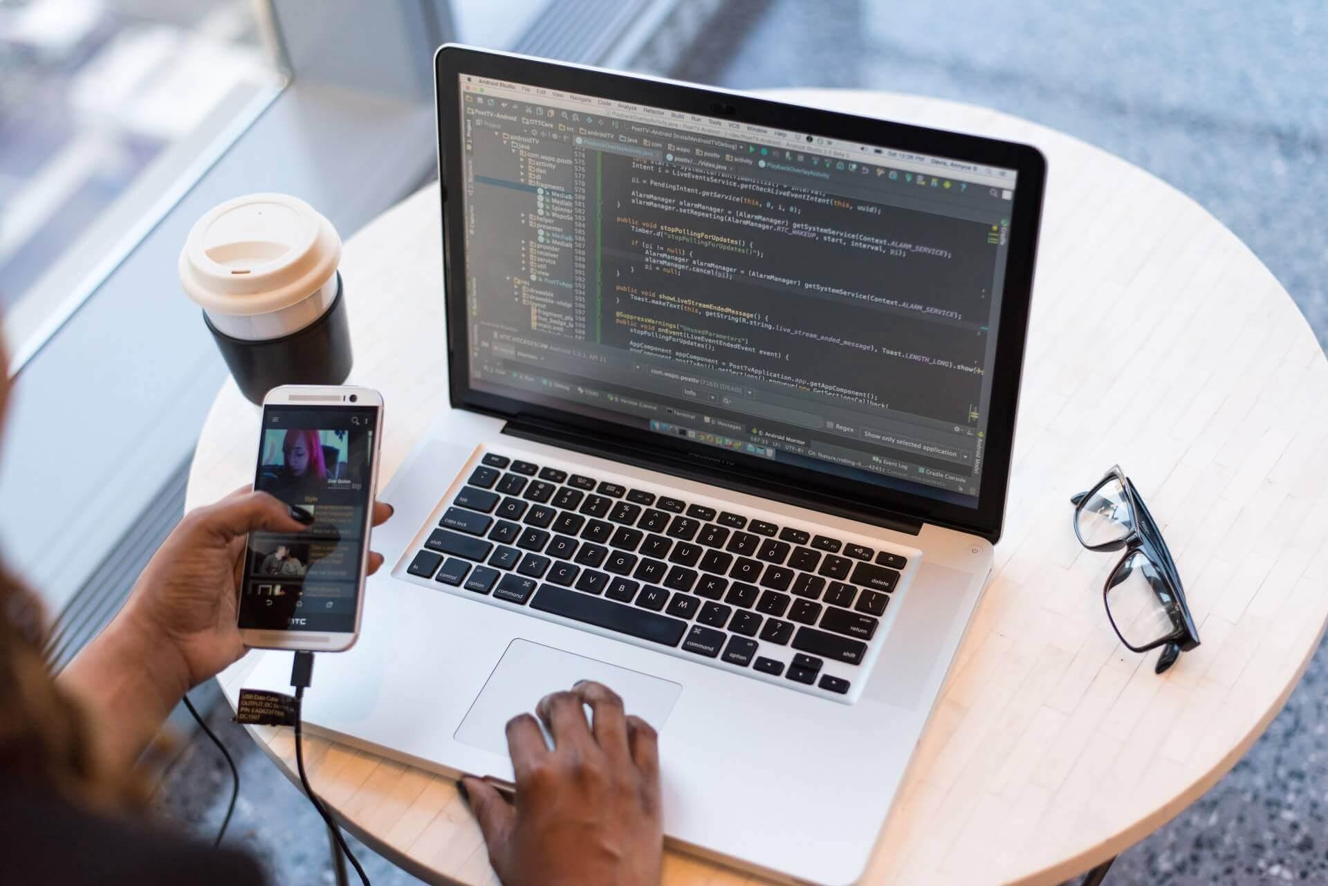 Facet korzystający z laptopa i telefonu